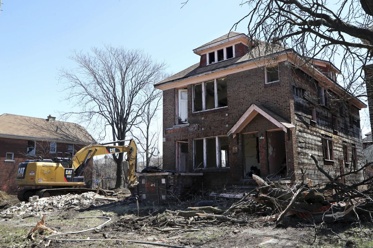 An excavator sits at the site of a house demolition in Detroit. There's dirt and fallen trees around the brick house, which has no windows or doors.