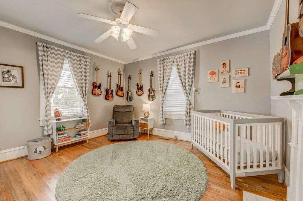 A bedroom with a crib and gray walls and many handing guitars.