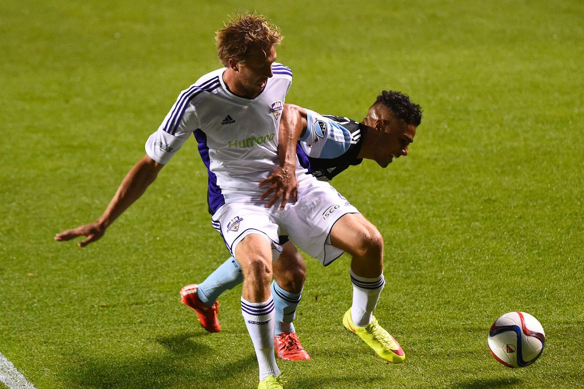 Louisville City right back Bryan Burke holds up a Chicago Fire player in a match from June.