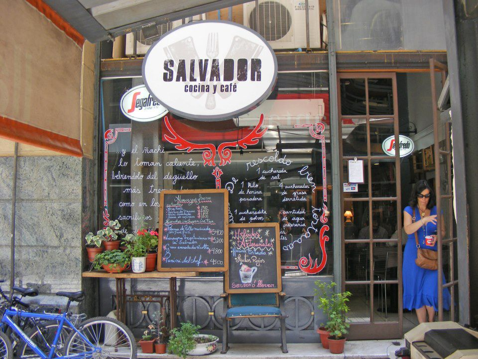 A restaurant exterior with large windows covered in writing, several chalkboards covered in more writing, a lit up sign reading Salvador, and a customer emerging from large mirrored doors to one side