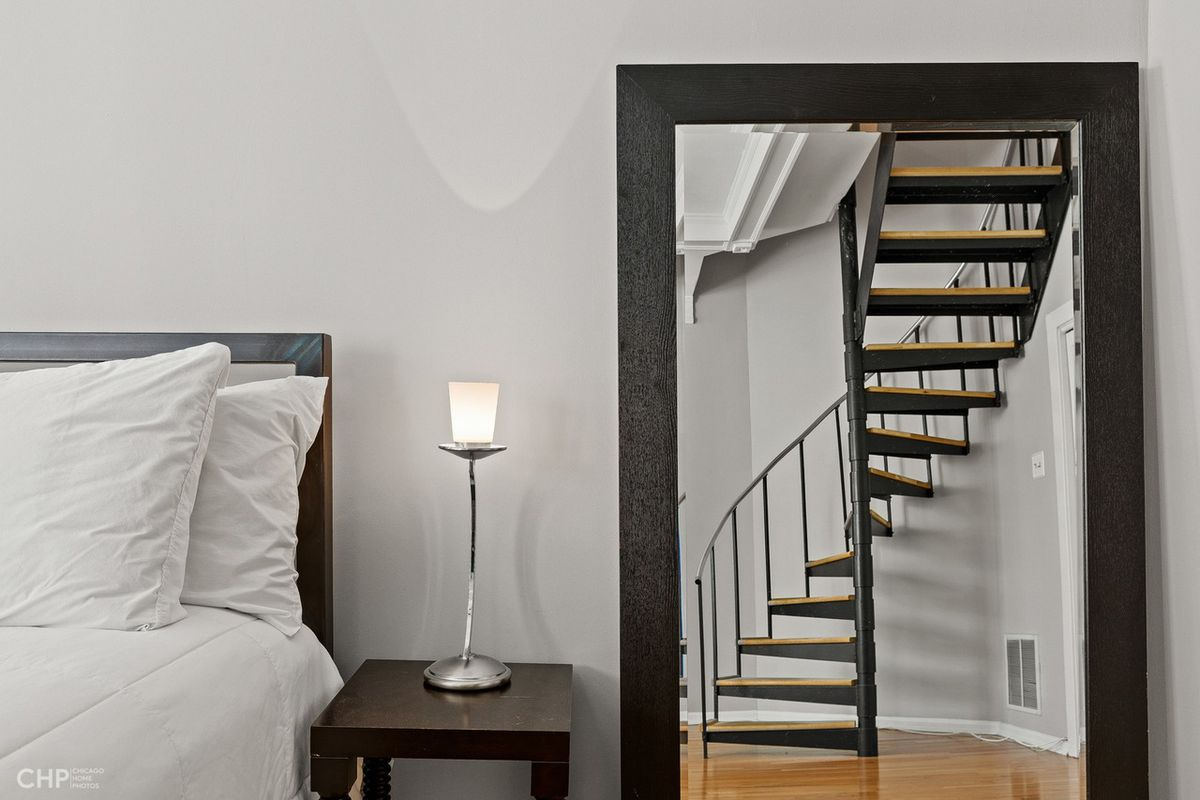 A close up view of the bed with a view of the spiral staircase in the mirror.