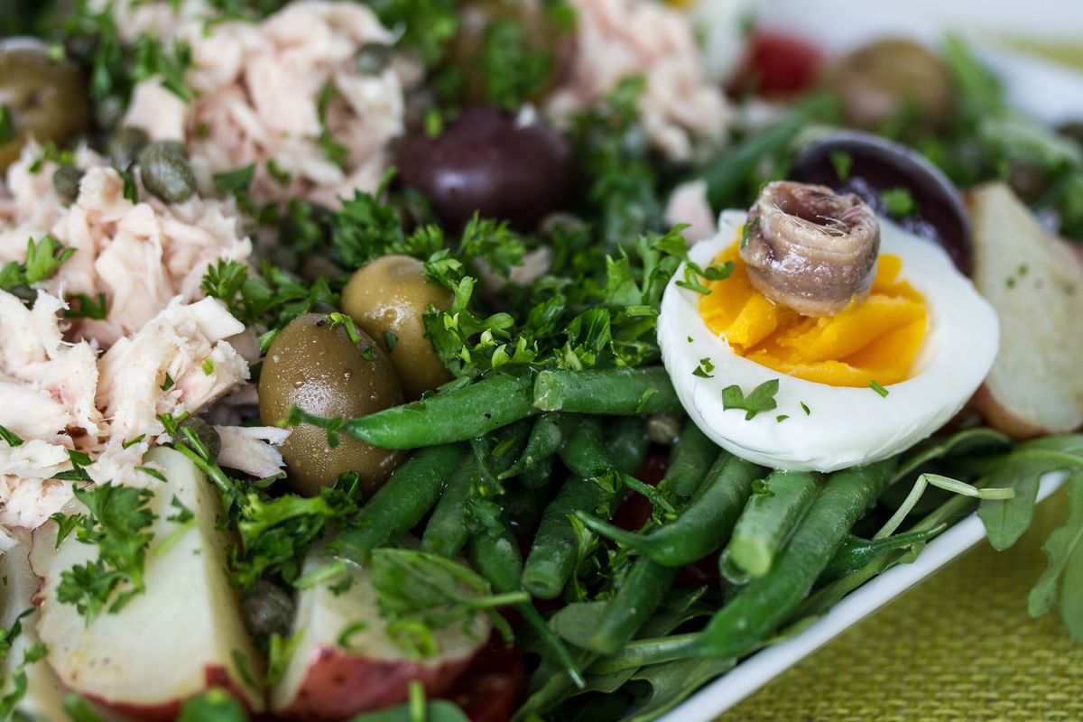 Salad Nicoise is traditionally made with hard-boiled eggs, Niçoise or Kalamata olives, tomatoes, anchovies (and sometimes tuna) and a vinaigrette dressing.