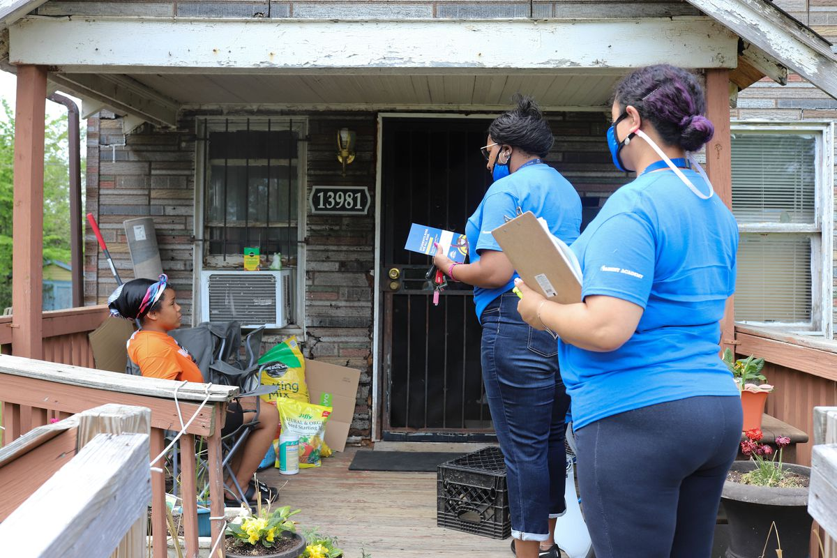 Two women wearing blue protective masks and shirts speak with a teenage girl on her front porch.