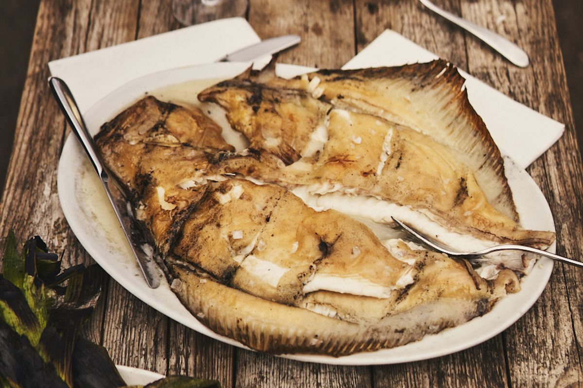 A whole grilled turbot presented on a white ceramic dish, on a wooden outdoor table