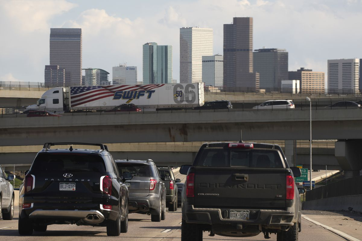 In this May 27, 2021 file photo, vehicles move along southbound Interstate 25 while motorists sit on the Interstate 70 overpass to start the Memorial Day weekend in Denver. Americans were hitting the road in near-record numbers at the start of the holiday weekend. More than 1.8 million people went through U.S. airports on Thursday, and that number could top 2 million over the weekend, the highest mark since early March of last year.