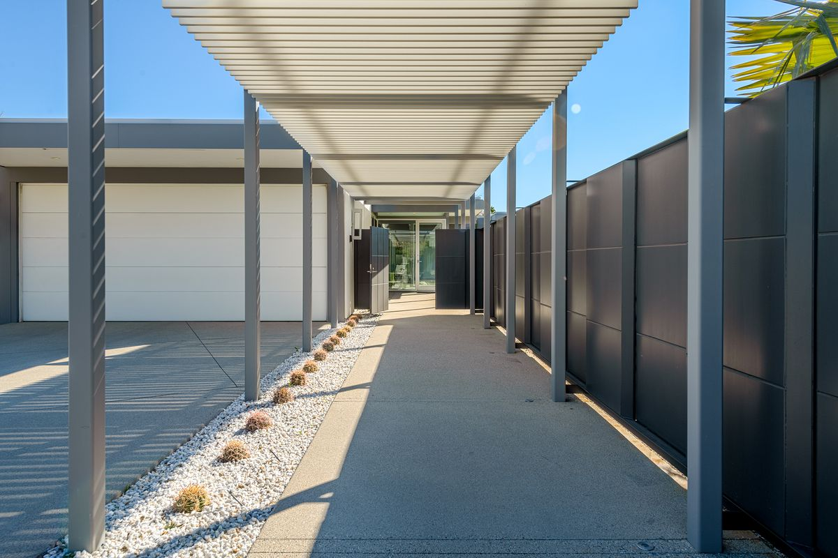 A covered walkway with steel beams provides an entrance to a midcentury-style home.