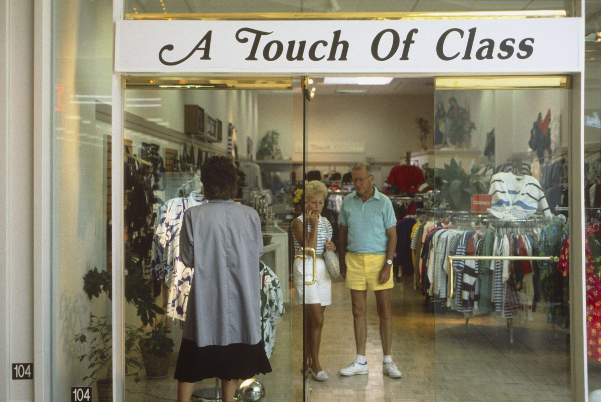 Shoppers stand inside a clothing store called Touch of Class.