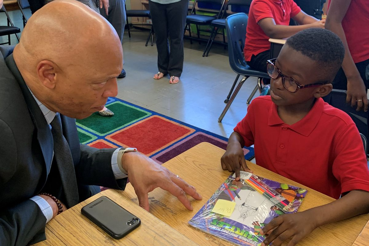 Superintendent William Hite discusses Ninja Turtles with Peter Ayodele, 8, a 3rd grader at Spruance Elementary School.