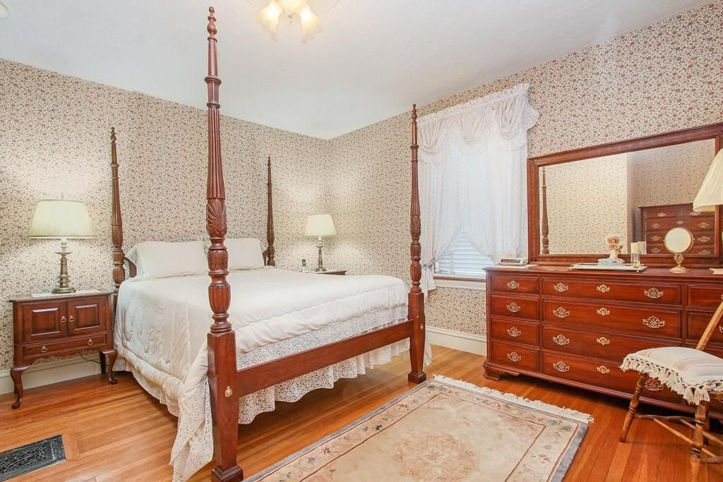 A bedroom with a dresser and a four-post bed.