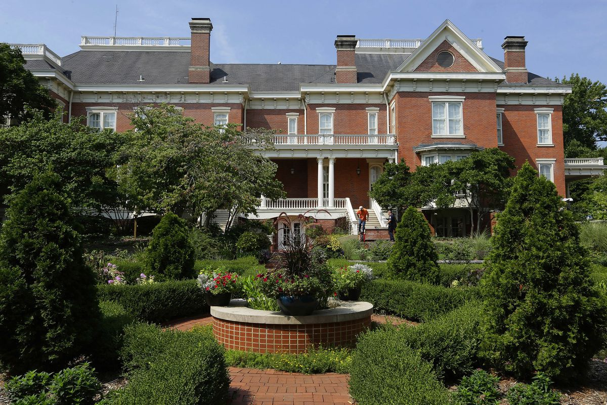 A large brick mansion for the governor of Illinois with a fountain in the foreground and lots of landscaped trees, bushes, and greenery.