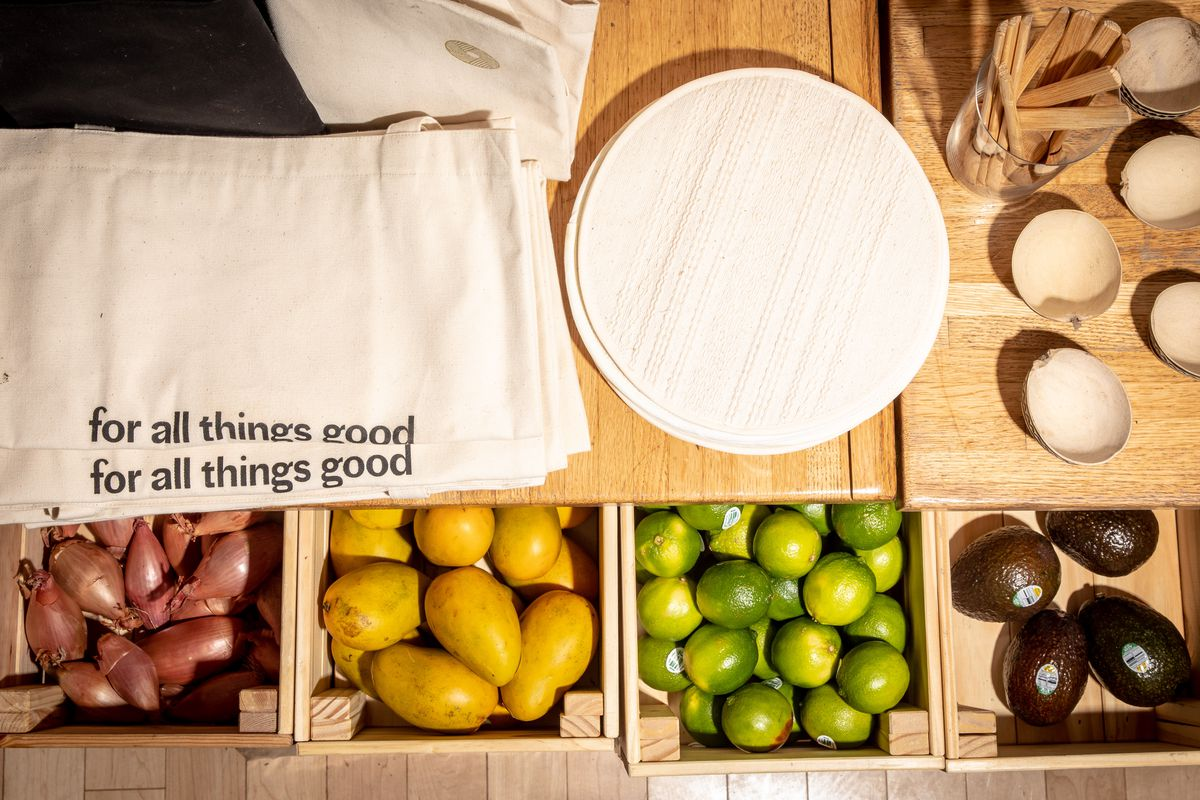 Limes, avocados, and totes are on display at this overhead shot of the tiendita, or corner store