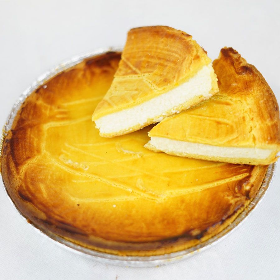 Two slices of ricotta pie with a white filling and light yellow char sit atop a full pie