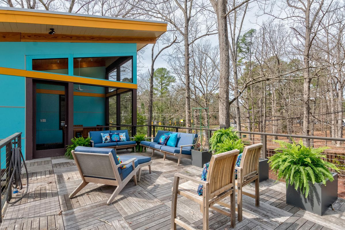 Outdoor chairs and lounge furniture sits on a rooftop patio next to a teal house.