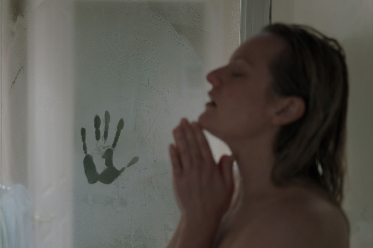 A woman stands in a shower while a handprint appears on the steamy shower door.