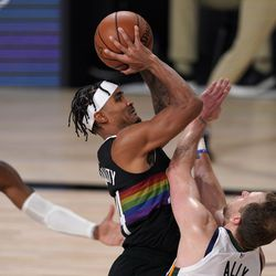 Denver Nuggets' Gary Harris (14) takes a shot as Utah Jazz's Donovan Mitchell (45) and Joe Ingles, right, defend during the first half an NBA first round playoff basketball game, Tuesday, Sept. 1, 2020, in Lake Buena Vista, Fla.