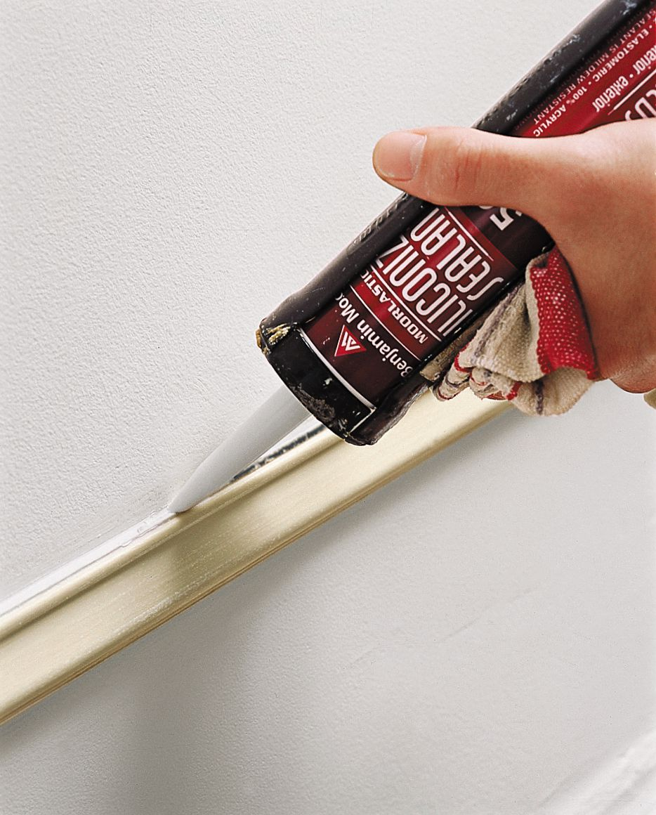 Filling gap in wall with caulk.