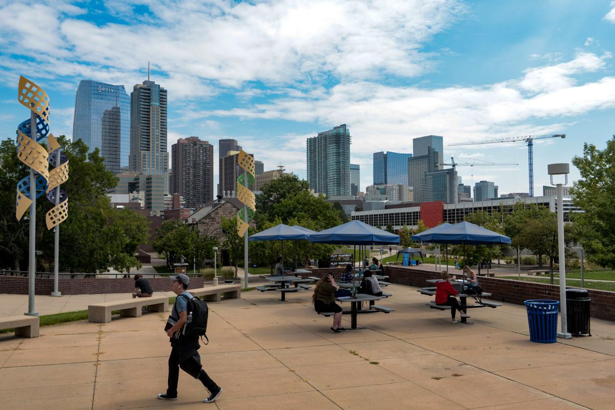 Students walk in a courtyard on a college campus with a skyline of skyscrapers in the background.