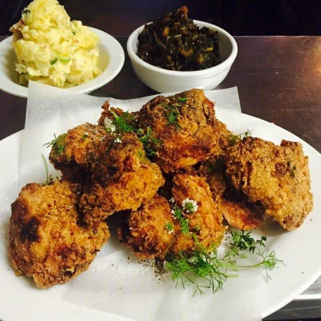 Hunks of fried chicken on butcher paper with diced herbs beside small bowls of potato salad and vegetables
