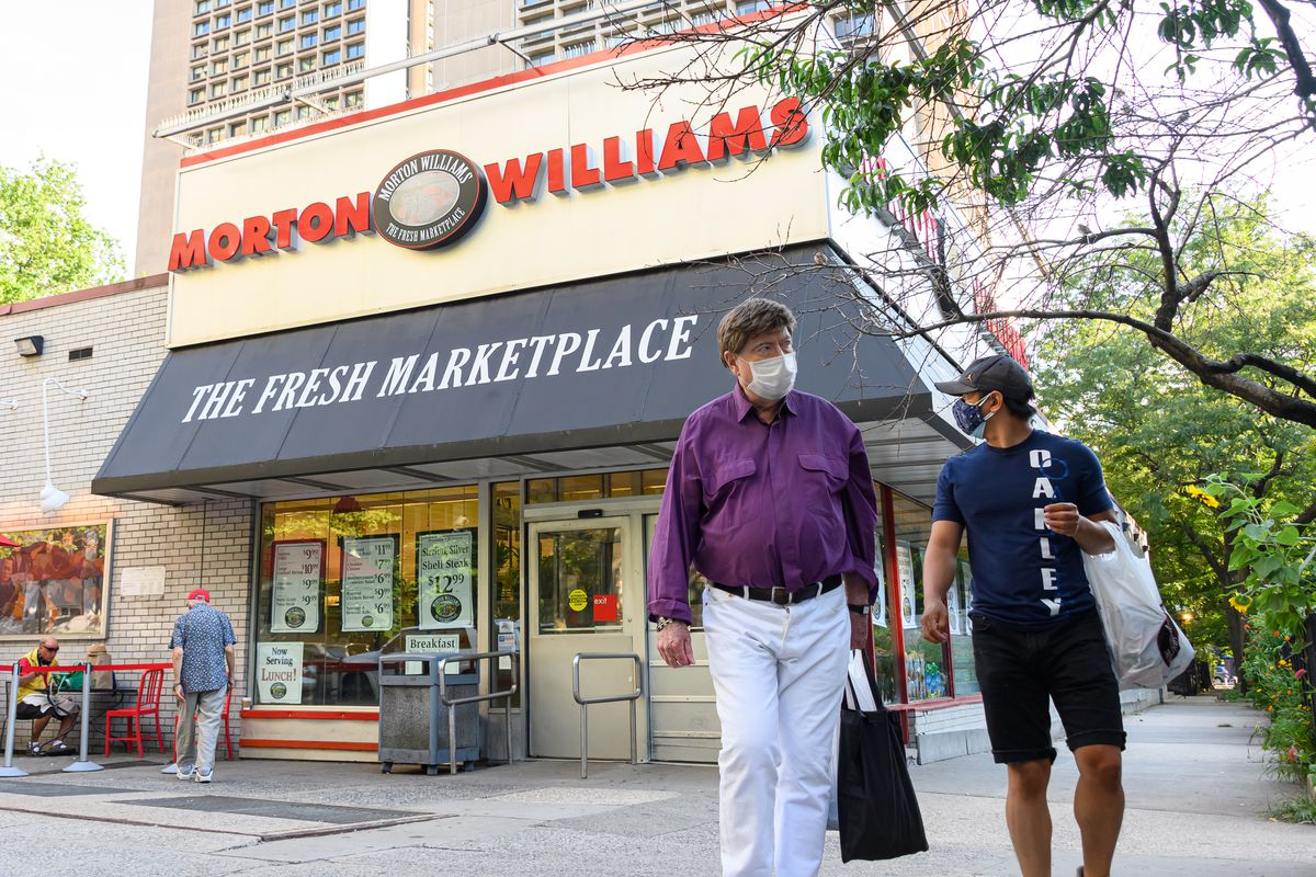 People wear protective face masks outside the Morton Williams supermarket in NoHo.