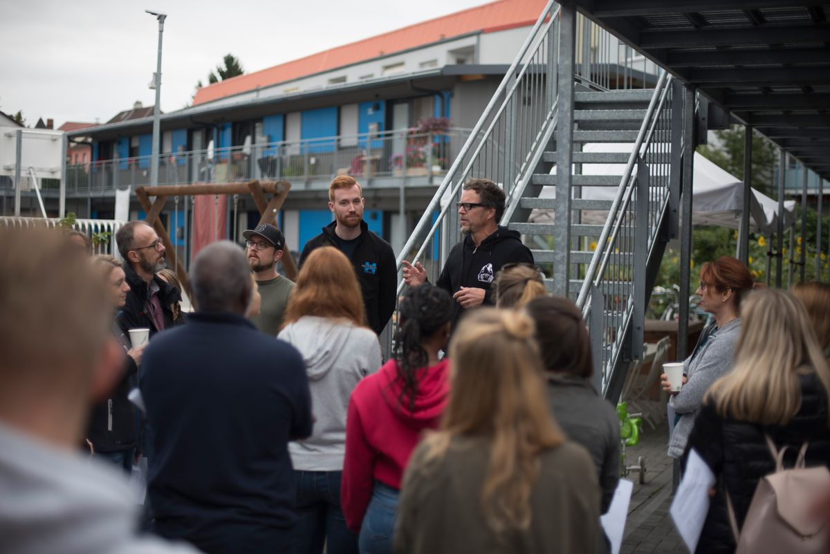 Refugee shelter director Thomas Müffke greets volunteers for a days of social service in Nied, Germany, on Friday, Sept. 13, 2019. The group was about to clean out a fresh space for a garden, plant trees, make some outdoor furniture and build some raised flower beds for the facility.