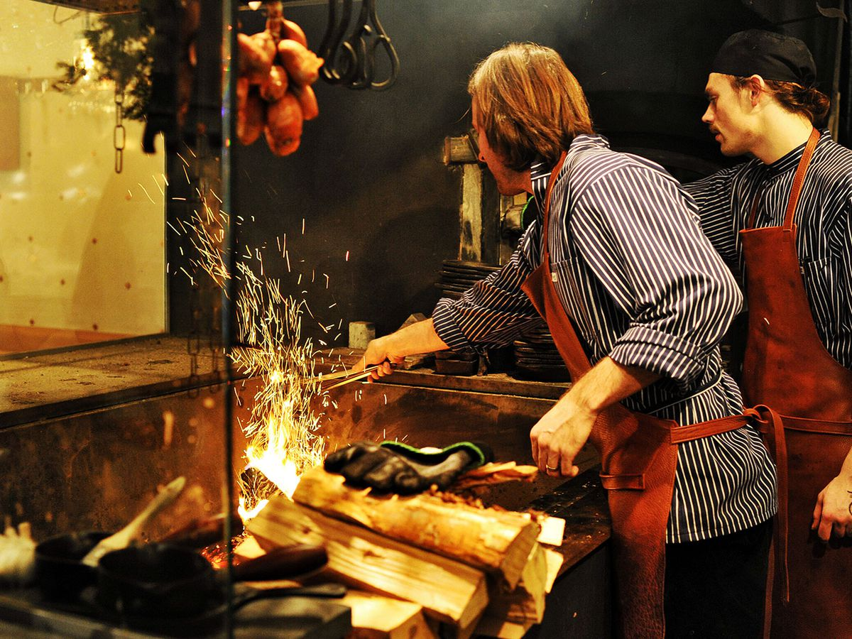 Chefs tend food on an open-flame fire pit