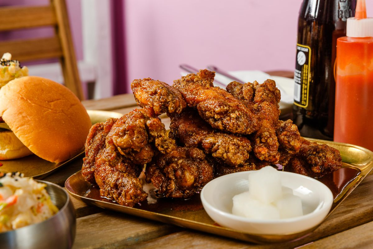 Mahogany-hued chicken wings sit atop one another on a tray, in this diagonal shot of the wings