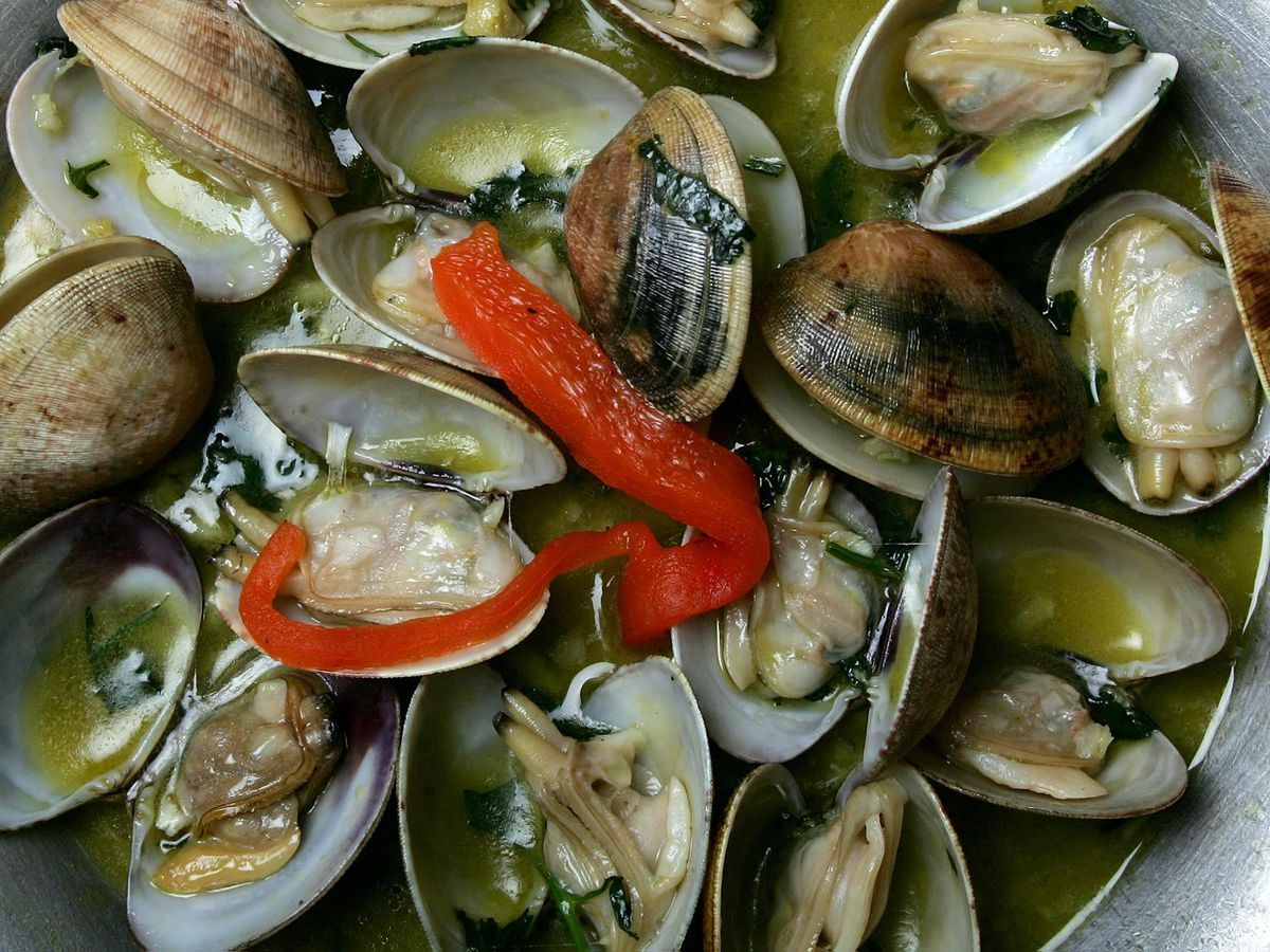 Cooked clams in broth with vegetables garnish
