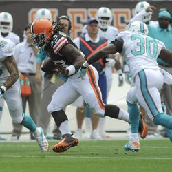 Sep 8, 2013; Cleveland, OH, USA; Cleveland Browns running back Trent Richardson (33) runs through Miami Dolphins strong safety Chris Clemons (30) and Miami Dolphins linebacker Jonathan Freeny (56) during the first quarter at FirstEnergy Stadium.