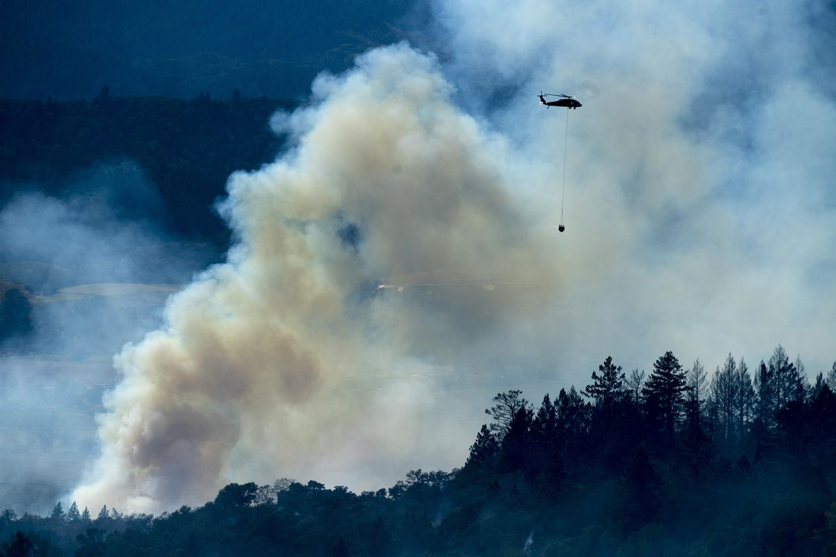 A large plume of smoke rises from a forest. A helicopter can be seen hovering in the smoke.