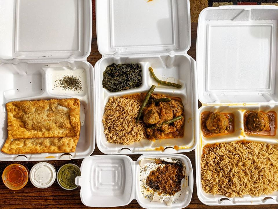 Overhead view of various types of Afghan food, delivered in white styrofoam containers —rice, meatballs, fried pastry shells, and more.