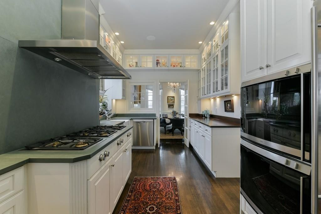 A long kitchen opening into another room and with counters on both sides.