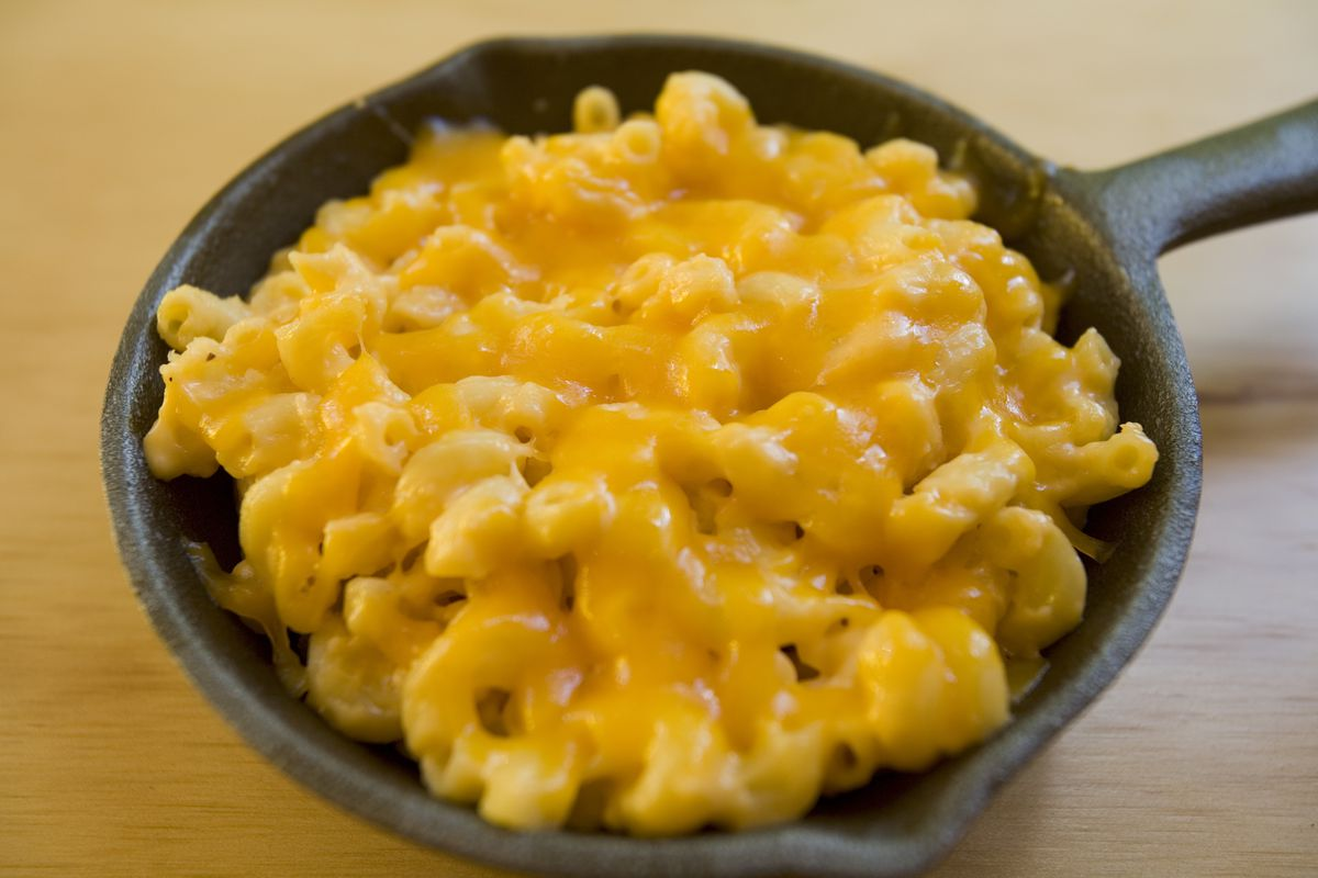 A black iron pan filled with yellow macaroni and cheese