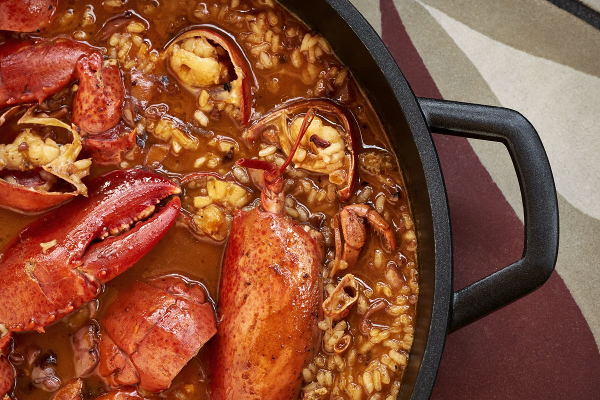 A Spanich rice dish with crab claws is a red sauce in a cast iron pot.
