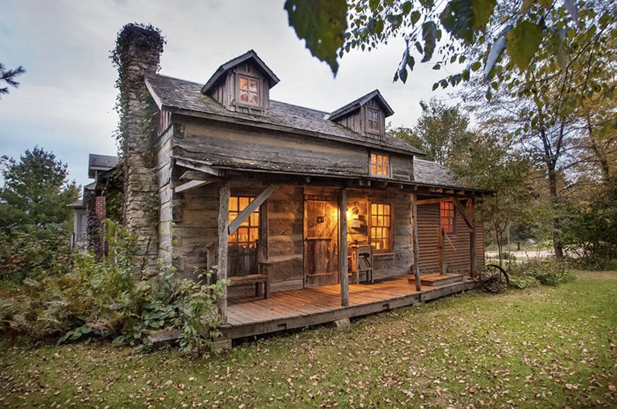 A cabin with a chimney, overgrown vines, and warm light coming from inside.