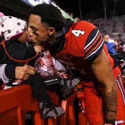 Utah Utes running back Troy McCormick Jr. (4) kisses his daughter, Eva McCormick, 10 months, before the game against the Colorado Buffaloes at Rice-Eccles Stadium in Salt Lake City on Saturday, Nov. 25, 2017.