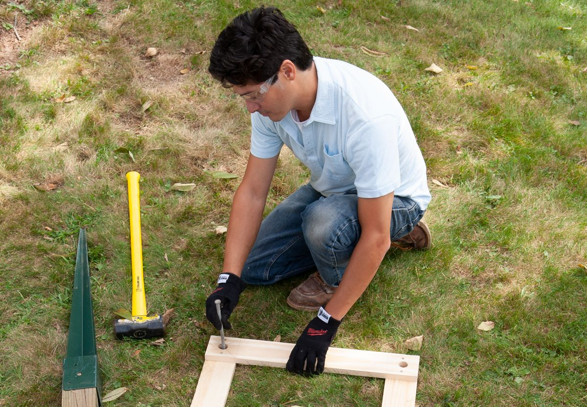 Man Makes Pilot Holes For Post Anchors To Build Garden Arbor With Bench