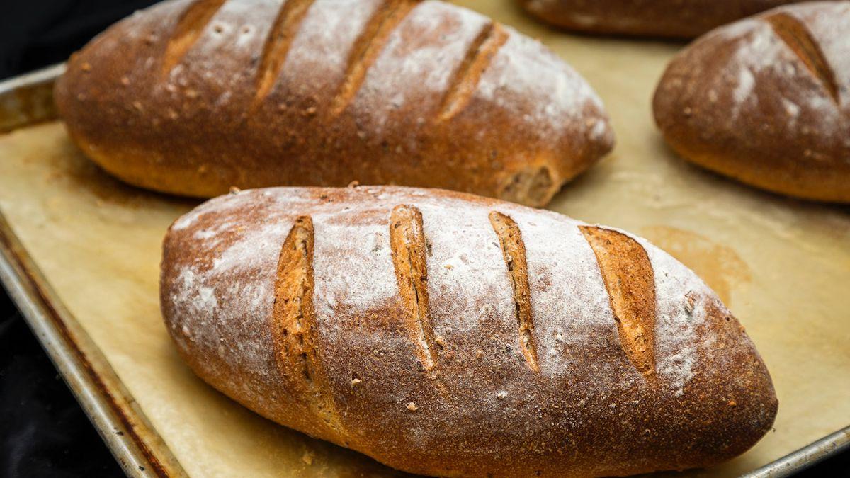 两粒新鲜的鲜被烘烤的大面包拂去用面粉拂去粉碎,得分在上面