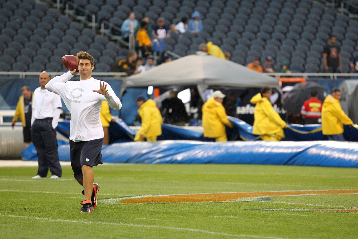 Aug 9, 2012; Chicago, IL, USA; Chicago Bears quarterback Jay Cutler (left) throws as the grounds crew removes the tarp from the field prior to the game against the Denver Broncos at Soldier Field.  Mandatory Credit: Matthew Emmons-US PRESSWIRE