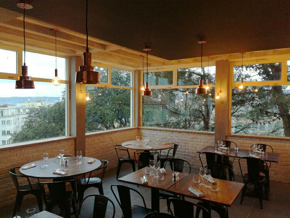 Trees and a cityscape outside the windows of an empty dining room, lit softly with pendants, featuring wooden tables of various shapes and low brick walls beneath the windows