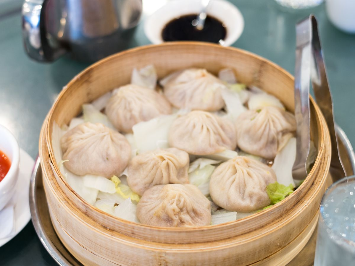 A wooden steamer basked with white parchment at the base. Eight off-white soup dumplings sit on top of it.