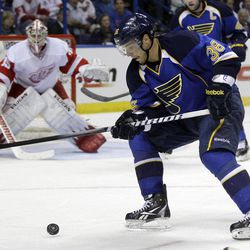 St. Louis Blues' Matt D'Agostini (36) controls the puck as Detroit Red Wings goalie Jimmy Howard, left, defends during the second period of an NHL hockey game on Wednesday, April 4, 2012, in St. Louis.