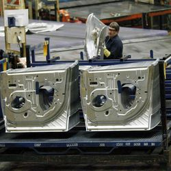 In this  Wednesday, April 4, 2012, photo, an auto worker at the Ford Stamping Plant stacks the inner door panel for the Ford Explorer in Chicago Heights. U.S. companies got more output from their workers this spring than initially thought. Productivity rose at a modest 2.2 percent annual rate in the April-June quarter, largely because employers cut back sharply on hiring.
