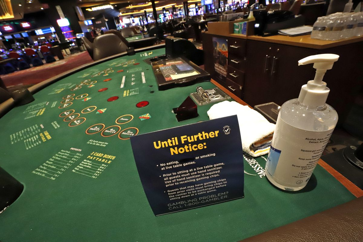 Hand sanitizer and a card explaining there will be no smoking or eating at gaming tables await the return of gamblers at Rivers Casino in Pittsburgh on Monday.