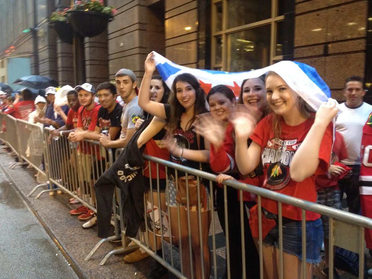 A city of Chicago flag helps keep the rain off these revelers on Monroe. | Rich Hein/Sun-Times