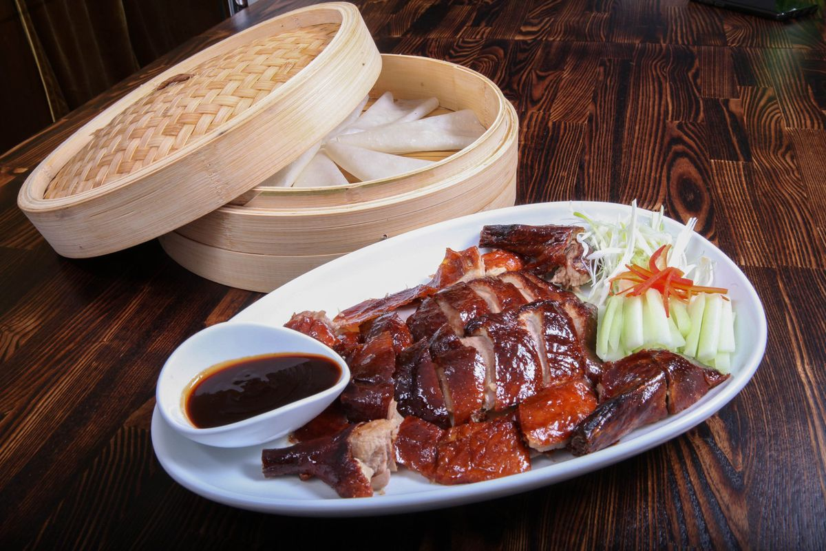 Peking duck on a white plate with a basket next to it
