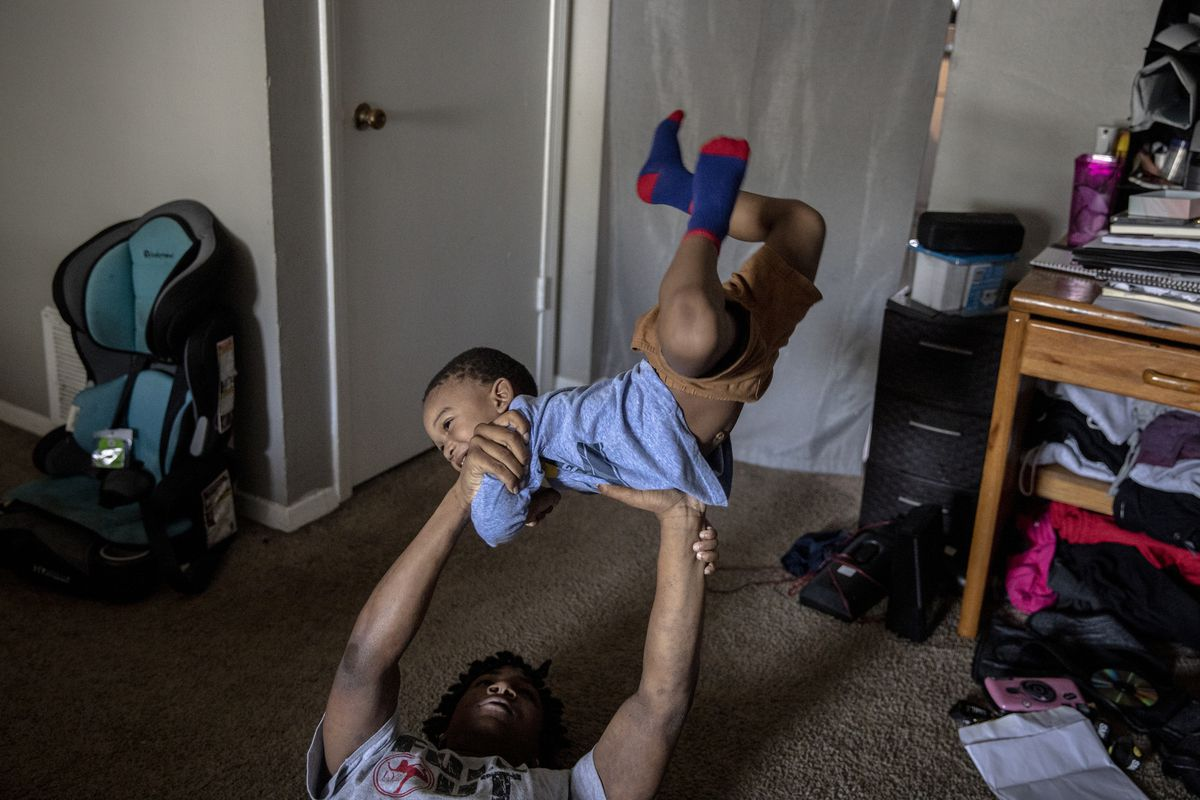 MEMPHIS, TN - March 16, 2021: Jalan Clemmons, a freshman at Hamilton High School, takes a break from schoolwork with his little brother while at home during a virtual school day. His mother, Anna Nuby, works from home and he also lives with his 2-year-old brother Kobi.