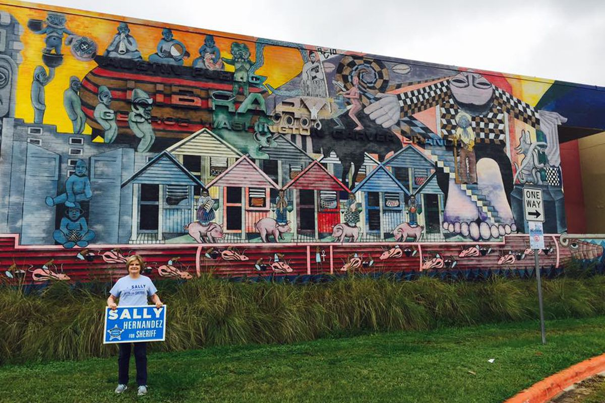 A white blond middle-aged woman with a blue Vote Sally Hernandez sign in front of a mural depicting Aztec and African-American figures and themes