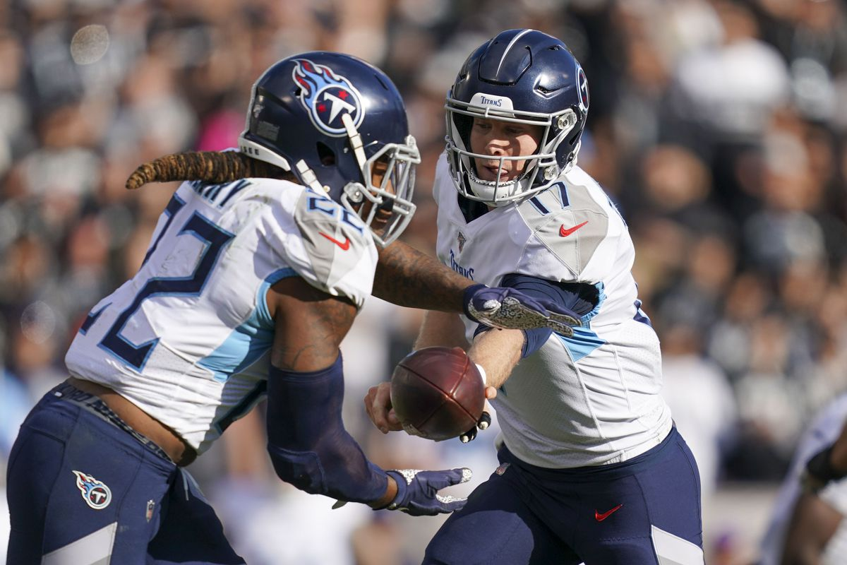 Tennessee Titans quarterback Ryan Tannehill hands the football off to running back Derrick Henry during the first quarter against the Oakland Raiders at Oakland Coliseum.