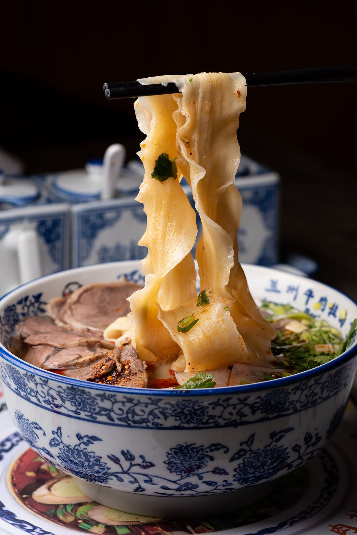 Wide noodles lifted up from a bowls of Lanzhou beef noodle soup with chopsticks.