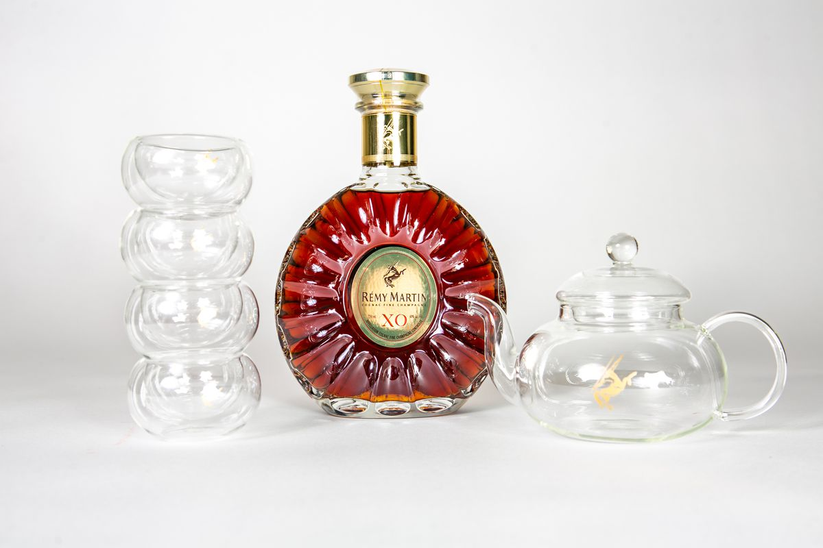 A bottle of Rémy Martin sits between four stacked glass teacups and a glass teapot.